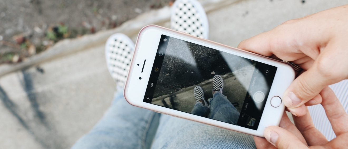 someone taking picture of shoes on phone