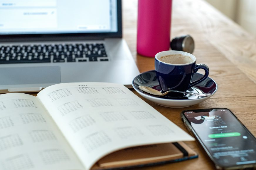 cup of coffee on a desk with a diary open